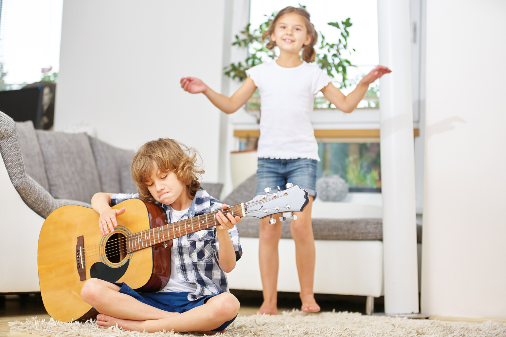 Boy playing guitar and girl dancing